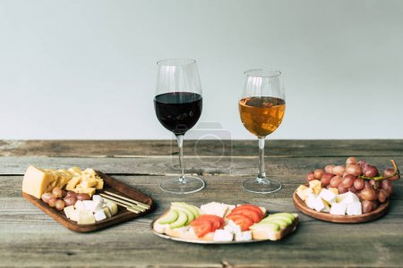 Glasses of wine and food on table