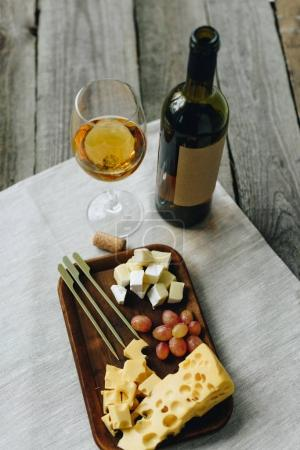 Glass with wine and plate with cheese and grapes