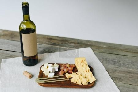 Wine bottle and plate with cheese and grapes