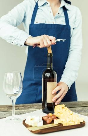 Woman opening bottle of white wine