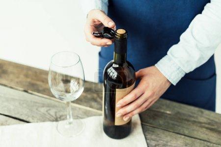sommelier opening bottle of white wine