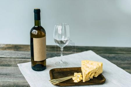 Wine bottle with empty glass and cheese