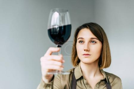 sommelier looking at glass of wine