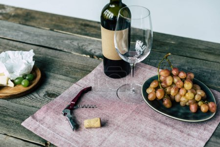 Wine bottle with empty glass and grapes
