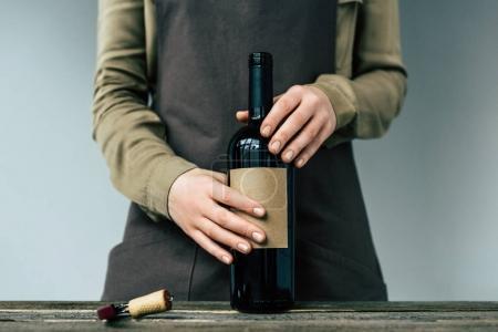Woman holding open bottle of wine
