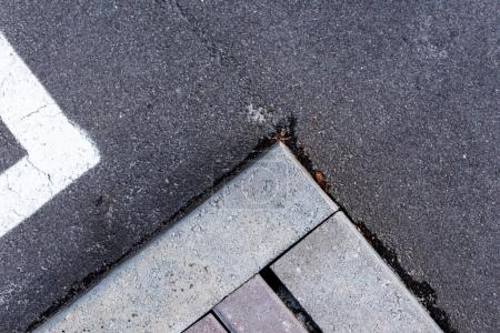 Photo for Concrete asphalt gray background with cracks and bricks - Royalty Free Image