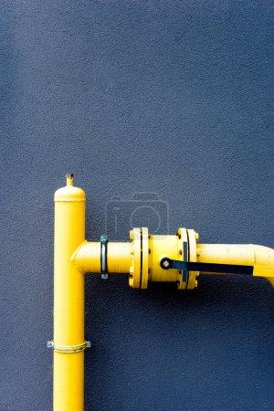 Photo pour Tuyau de gaz jaune devant un mur bleu - image libre de droit