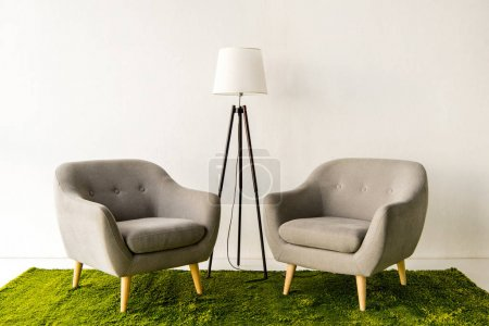 armchairs and lamp on green carpet