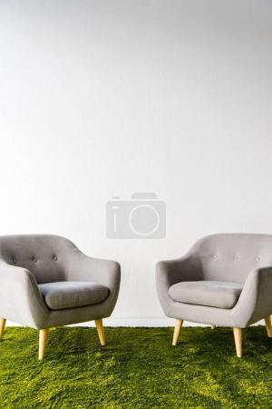 Two armchairs on carpet