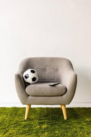 Football ball and remote controller on armchair