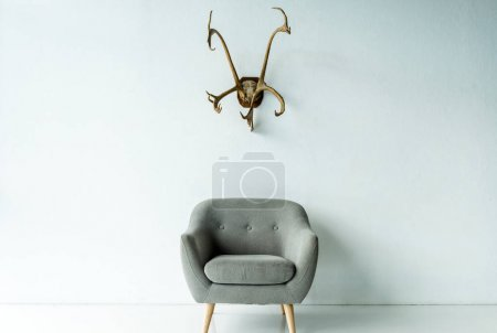 armchair and antlers on wall