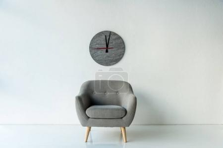 Photo for Empty armchair on a floor and art clock on a wall - Royalty Free Image