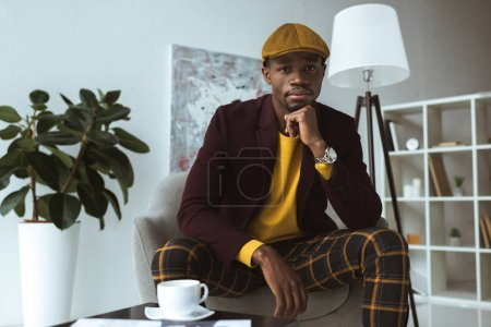 Photo for Pensive stylish african american businessman in cap with coffee cup sitting in armchair in modern office - Royalty Free Image