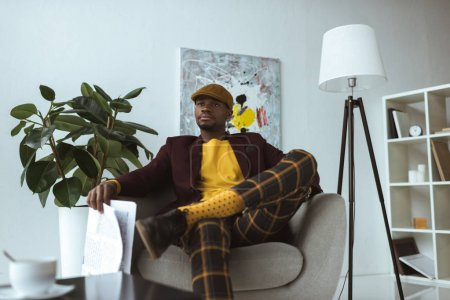 stylish african american businessman with newspaper