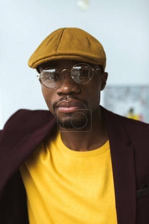 Photo pour Portrait de bel homme afro-américain à la mode en casquette et lunettes regardant la caméra - image libre de droit