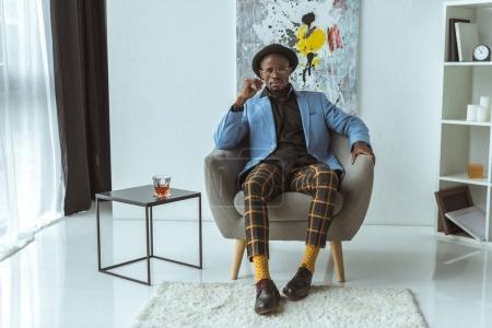 fashionable man sitting in armchair