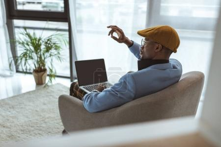 Photo for Stylish african american man gesturing and working with laptop in modern office - Royalty Free Image