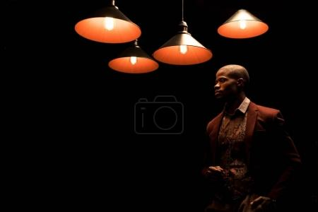 Photo for Elegant african american man in jacket isolated on black with lamps - Royalty Free Image