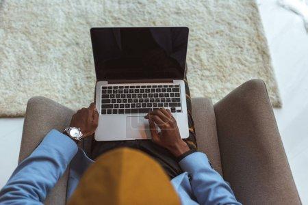 Photo pour Vue aérienne de l'élégant homme afro-américain utilisant ordinateur portable avec écran blanc - image libre de droit