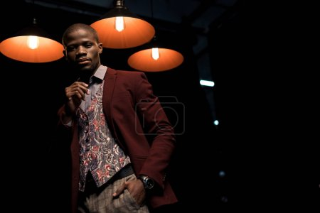 Photo for Stylish elegant african american man in jacket isolated on black with lamps - Royalty Free Image