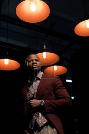 stylish man in dark room with lamps