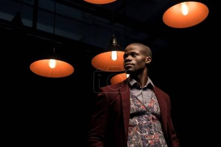 african american man in dark room with lamps