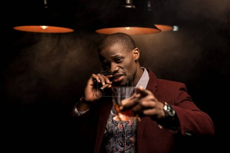 Photo for Luxury african american man smoking cigar and drinking whiskey in dark room with lamps - Royalty Free Image