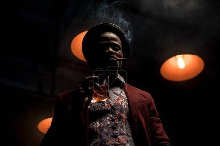 Photo pour Bel homme afro-américain de luxe en chapeau fumant du cigare et buvant du whisky dans une pièce sombre avec des lampes - image libre de droit