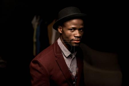Photo for Handsome fashionable african american man in hat looking at camera in dark room - Royalty Free Image