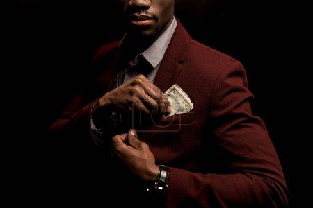 Photo pour Vue recadrée riche afro-américain de mettre des billets de dollar en poche isolée sur fond noir - image libre de droit