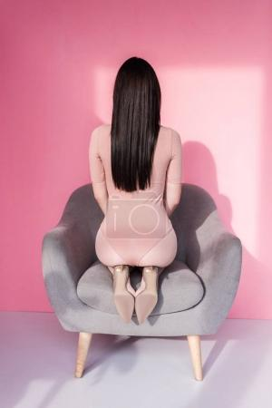Photo for Back view of young woman in bodysuit kneeling on chair - Royalty Free Image