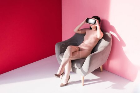 Photo for Beautiful young woman in bodysuit and high heeled shoes using vr headset on pink - Royalty Free Image