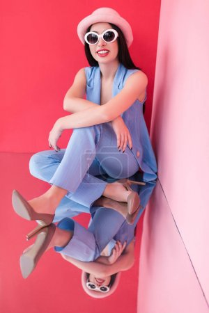 Photo for Beautiful stylish young woman in hat and sunglasses smiling at camera in studio - Royalty Free Image