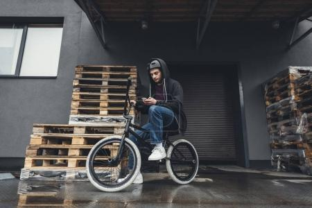 Photo for Full length view of bmx biker sitting on bicycle and using smartphone on street - Royalty Free Image