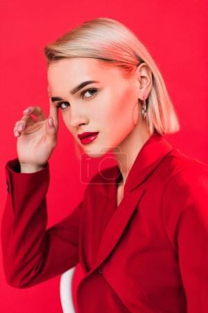 Photo pour Blonde élégante fille posant en veste rouge, isolé sur rouge - image libre de droit