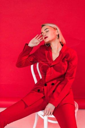 elegant girl posing in red suit