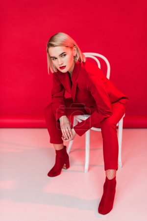 Photo for Fashionable elegant girl posing in red suit, on red - Royalty Free Image