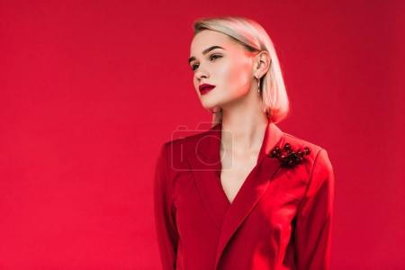 Photo for Beautiful stylish girl in red jacket with boutonniere, isolated on red - Royalty Free Image