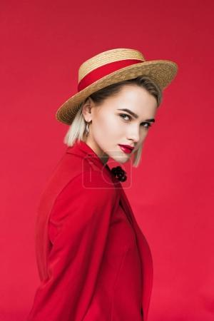 Photo for Attractive girl in red jacket and straw hat, isolated on red - Royalty Free Image