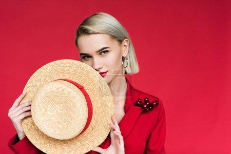 Photo pour Belle fille à la mode en veste rouge avec boutonnière et chapeau de paille, isolé sur rouge - image libre de droit