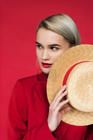 Photo for Attractive stylish girl in red jacket with straw hat, isolated on red - Royalty Free Image