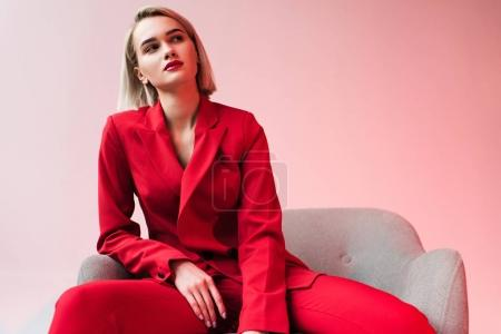 Photo for Elegant fashionable woman in red clothes posing in armchair, on pink - Royalty Free Image