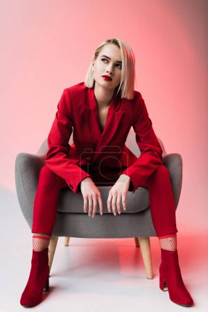 Photo for Elegant stylish woman in red clothes posing in armchair, on pink - Royalty Free Image