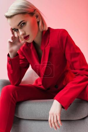 Photo pour Jolie femme élégante élégante en vêtements rouges, posant en fauteuil, isolé sur rose - image libre de droit
