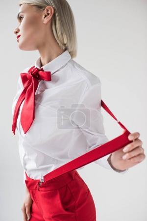 Photo pour Élégante femme élégante qui pose en chemise blanche, bretelles rouges et arc, isolé sur fond gris - image libre de droit