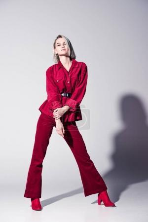 Photo pour Jolie fille élégante de vêtements à la mode rouges posant pour Shooting de mode, sur fond gris - image libre de droit