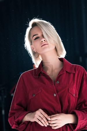 Photo for Attractive elegant girl in red trendy clothes, on black with back light - Royalty Free Image