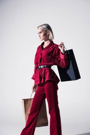 Photo pour Belle fille élégante de vêtements à la mode rouges avec des sacs à provisions, isolés sur fond gris - image libre de droit