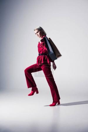 Foto de Hermosa chica de moda en ropa de moda rojo con bolsas de compras, en gris - Imagen libre de derechos