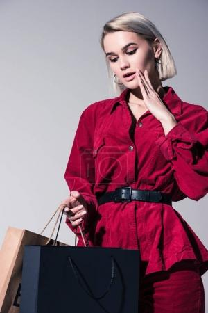 Photo pour Jolie fille à la mode dans les vêtements à la mode rouges avec des sacs à provisions, sur fond gris - image libre de droit